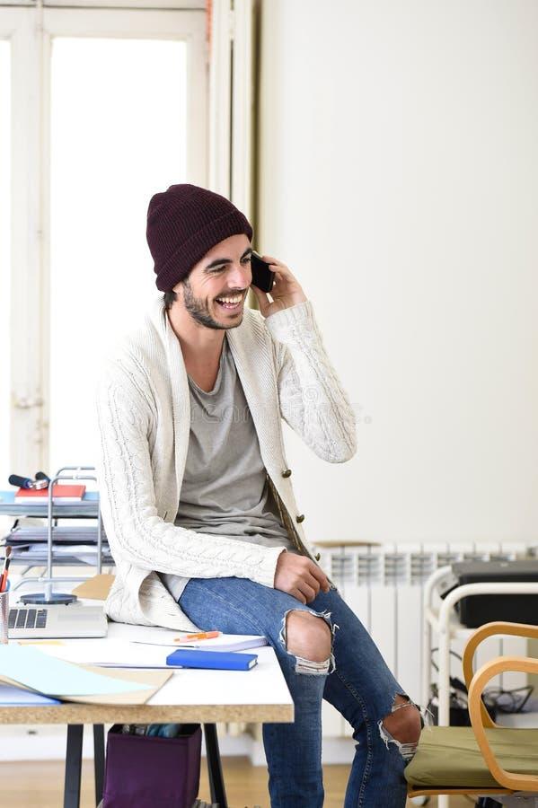 Modischer Geschäftsmann in der informellen Blickunterhaltung des Beanie und des kühlen Hippies glücklich am Handy lizenzfreie stockfotos