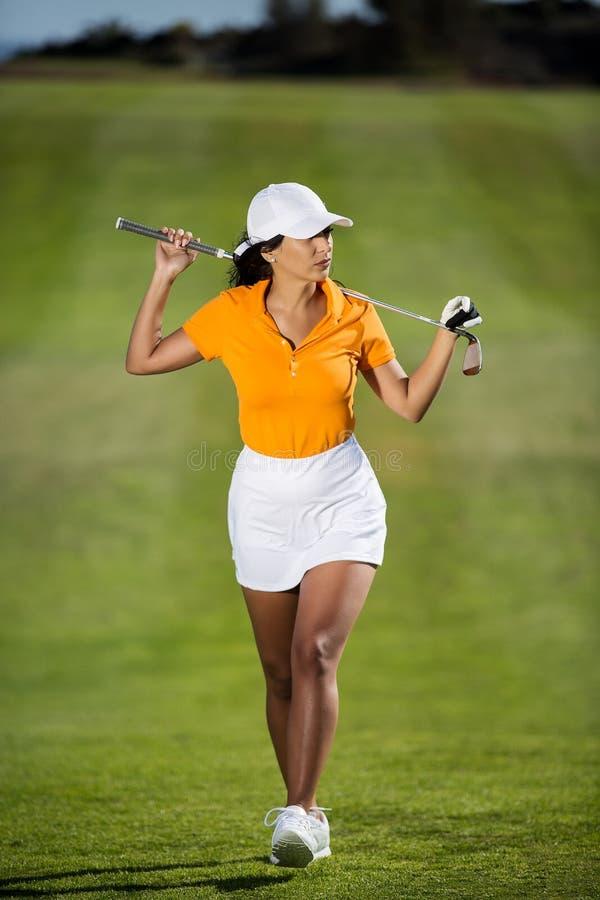 Modischer Golfspieler mit Fahrer auf Feld lizenzfreie stockbilder