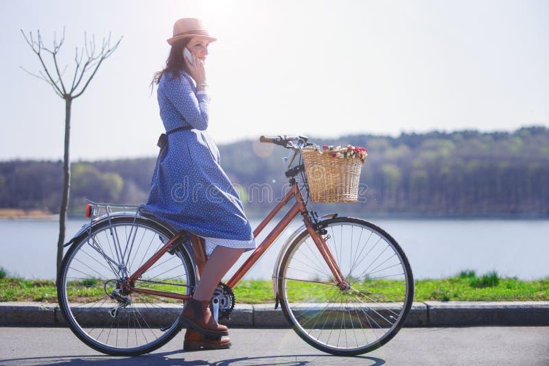 Modischer Halt der jungen Frau zum Fahren auf ihr Weinlesefahrrad mit Korb von Blumen während fokussiertes am intelligenten Telef stockfoto