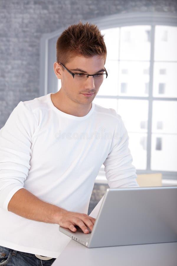 Modischer junger Mann mit Laptop stockbild