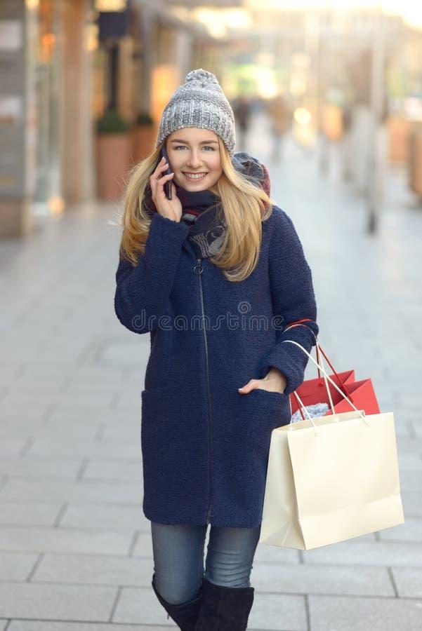 Modischer Käufer der jungen Frau, der ihr Mobile verwendet stockfoto