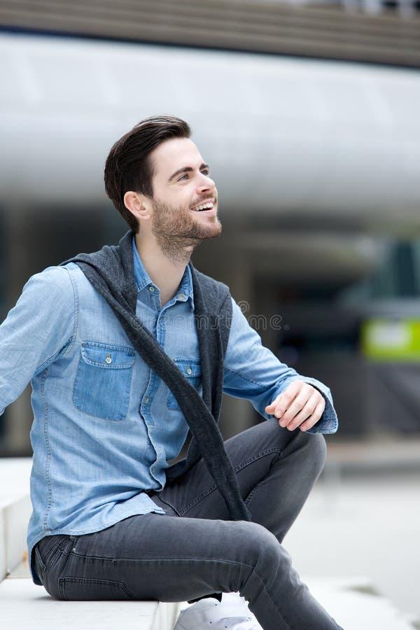 Modischer Kerl, der draußen sitzt stockfotos