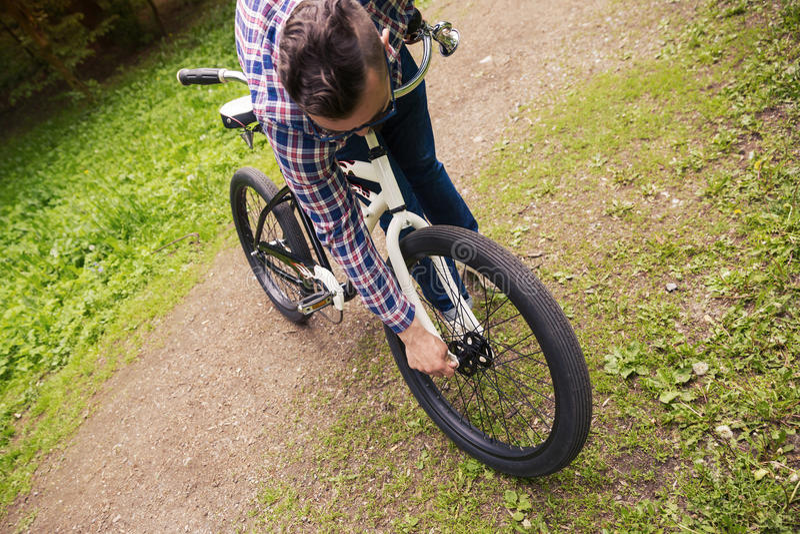 Modischer Mann, der Fahrradfelge am Park repariert stockbild