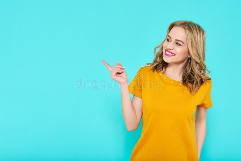 Modisches attraktives Senffarbsommerkleid der jungen Frau tragendes, das über blauem Pastellhintergrund aufwirft Vorderansicht de lizenzfreie stockfotos