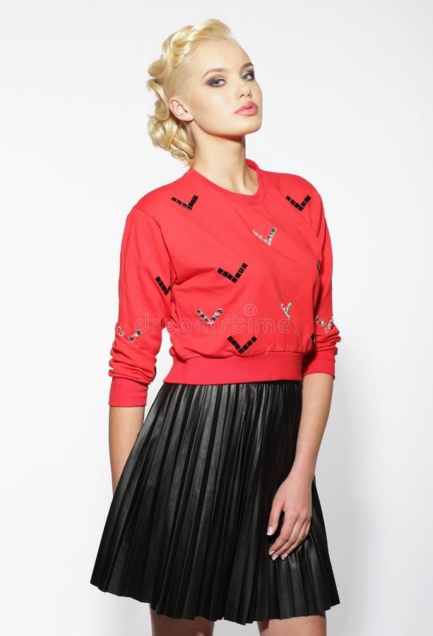 Modisches blondes in der roten Bluse und im schwarzen Rock stockfotos