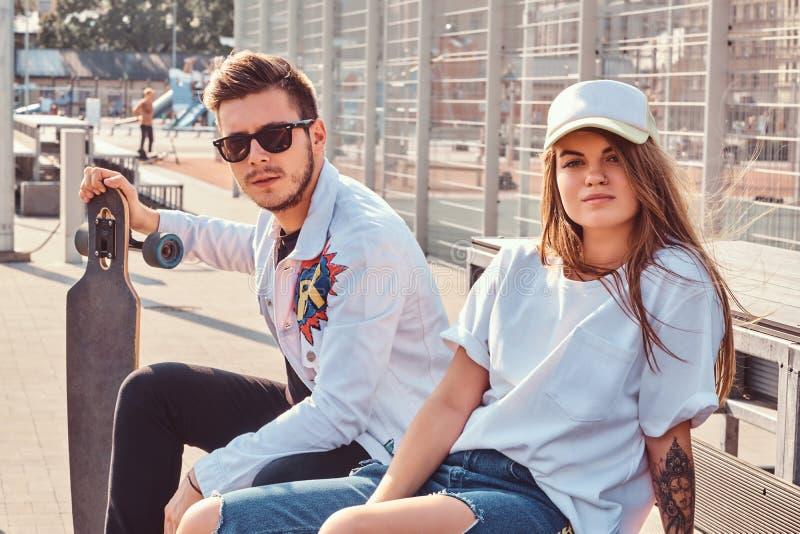 Modisches gekleidetes junges Paar mit den Skateboards, die auf einer Bank an der Stadt sitzen, trägt Komplex am sonnigen Tag zur  stockbild