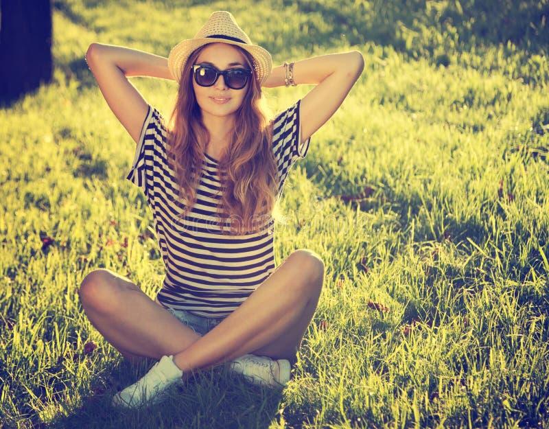 Modisches Hippie-Mädchen, das auf dem Gras sich entspannt stockbilder