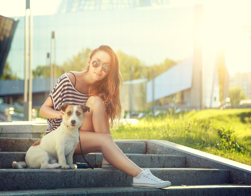 Modisches Hippie-Mädchen mit ihrem Hund in der Stadt stockbild