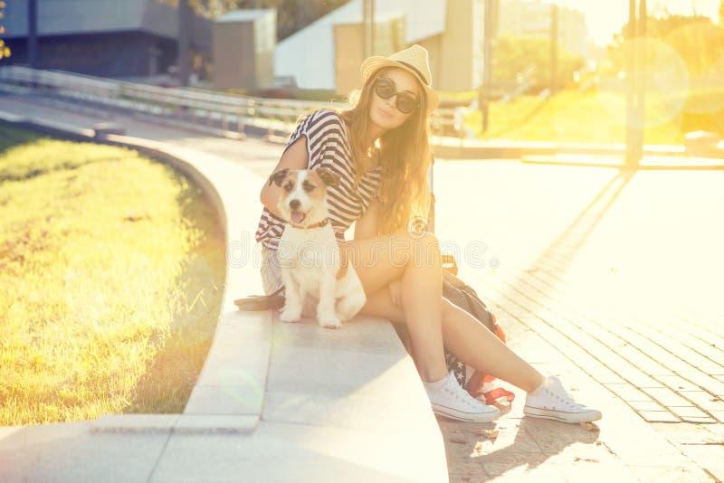 Modisches Hippie-Mode-Mädchen mit Hund in der Stadt lizenzfreie stockbilder