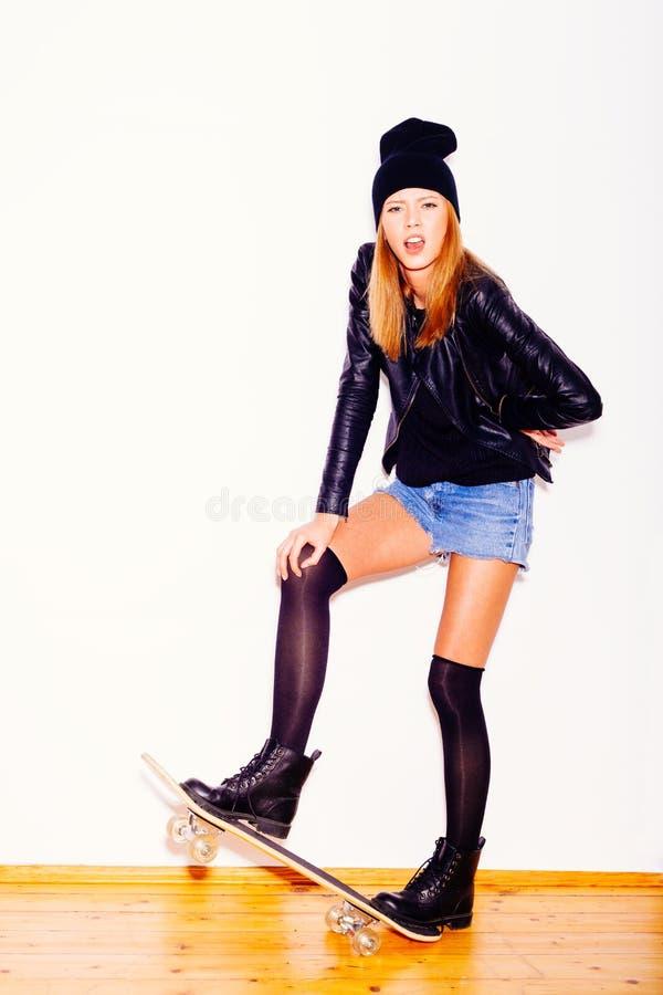 Modisches Mädchen in der schwarzen Jacke und im Beanie mit Skateboard stockbilder