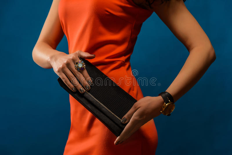 Modisches Mädchen nahe stilvollem rotem Kleid und Kupplung des blauen Hintergrundes lizenzfreies stockbild