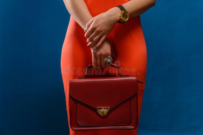 Modisches Mädchen nahe stilvollem rotem Kleid und Kupplung des blauen Hintergrundes stockbild