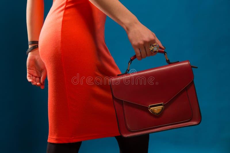Modisches Mädchen nahe stilvollem rotem Kleid und Kupplung des blauen Hintergrundes stockfotografie