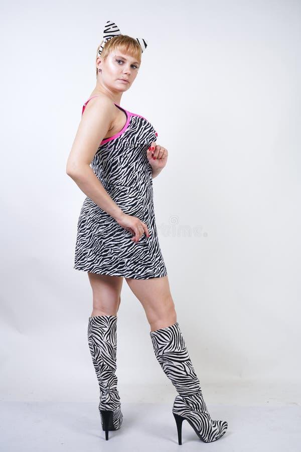 Modisches Plusgrößenmädchen mit dem kurzen blonden Haar in einem Zebradruckkleid, lustigen in Fantasiepelzohren und in einem Tier stockbild