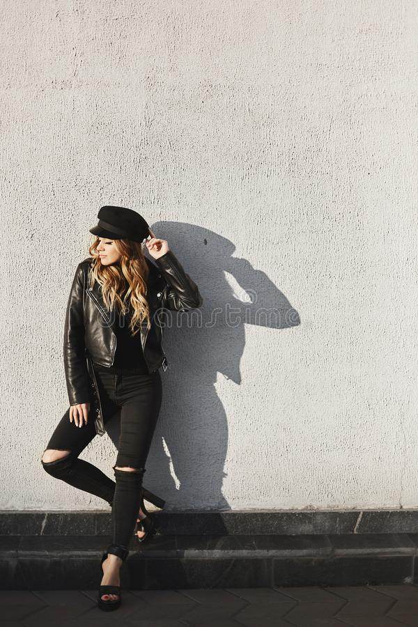 Free Modish Blonde Model Girl In A Leather Jacket, Ripped Jeans, And Black Cap Standing Outdoors Against The Urban Wall In Royalty Free Stock Photo - 162431465