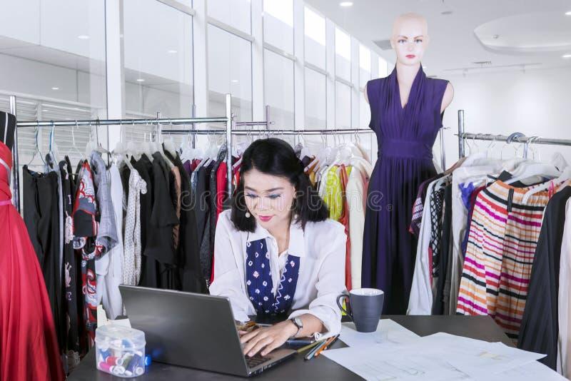 Modista de sexo femenino que mecanografía en un ordenador portátil fotos de archivo libres de regalías