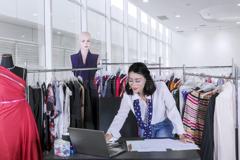 Modista de sexo femenino que trabaja en el lugar de trabajo imagen de archivo libre de regalías