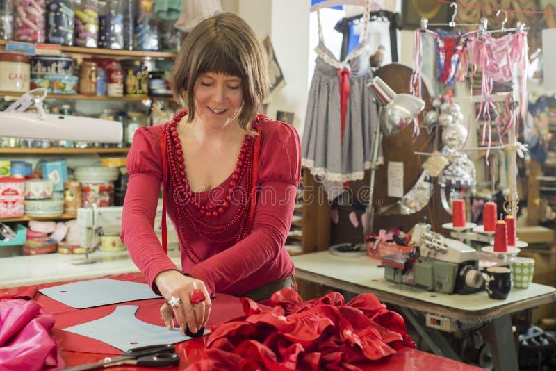 Modista en vestido y de los collares paño de trazo rojos feliz fotografía de archivo libre de regalías