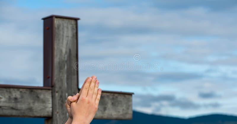 Modlenie chłopiec młoda ręka w ostrości, prosty drewniany katolika krzyż obrazy royalty free