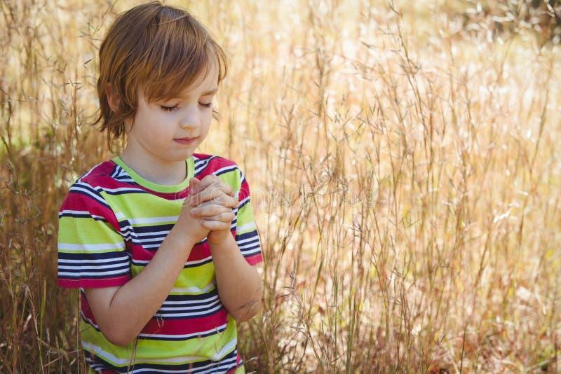 Modlenie chłopiec w parku obraz royalty free