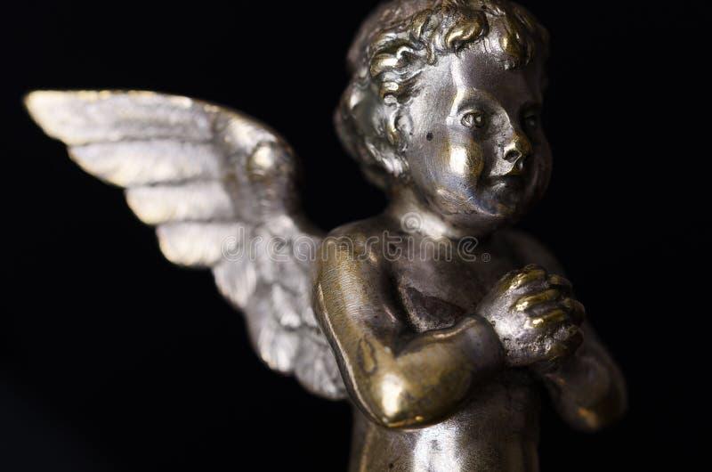 Modlenie mosiężnego anioła boczny widok nad czernią zdjęcie stock