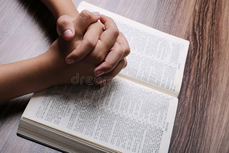 Modlić się ręki Z Świętą biblią zdjęcie stock