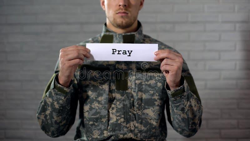 Modli się słowo pisać dalej podpisuje wewnątrz ręki męski żołnierz, żołnierz pyta dla pokoju obrazy stock