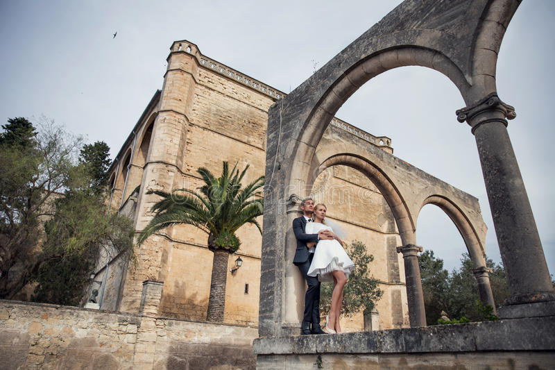 Modna ślub para blisko kościół katolickiego pannę młodą ceremonii ślub kościelny pana młodego na terenach odkrytych portret obrazy stock