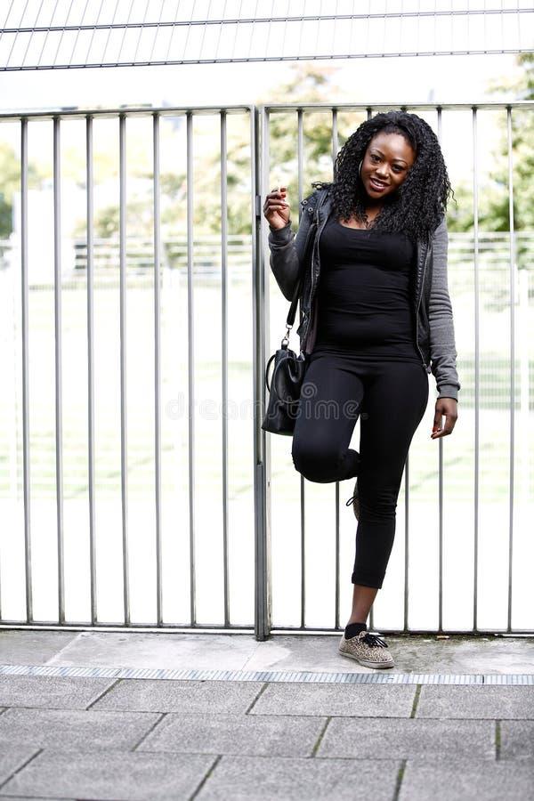 Modna Afrykańska dama pozuje przed poręczami fotografia royalty free