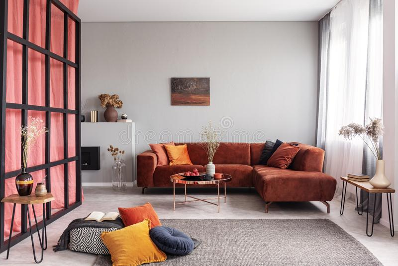 Modna aksamita kąta kanapa z poduszkami obok eleganckiego stolika do kawy z kwiatami obrazy royalty free