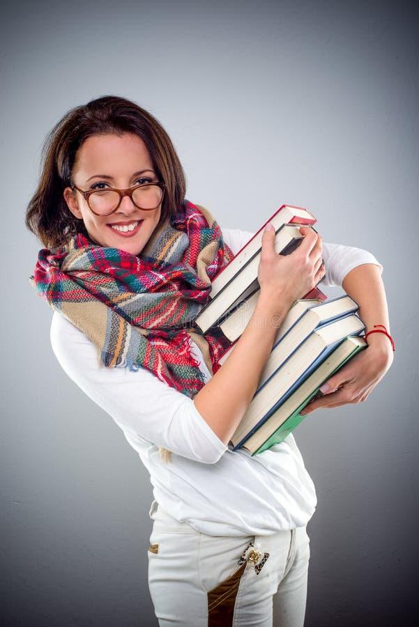 Modna atrakcyjna kobieta niesie stos książki obrazy stock