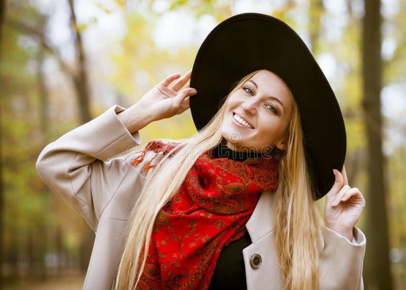 Modna blond kobieta przy piękną jesieni aleją obraz royalty free