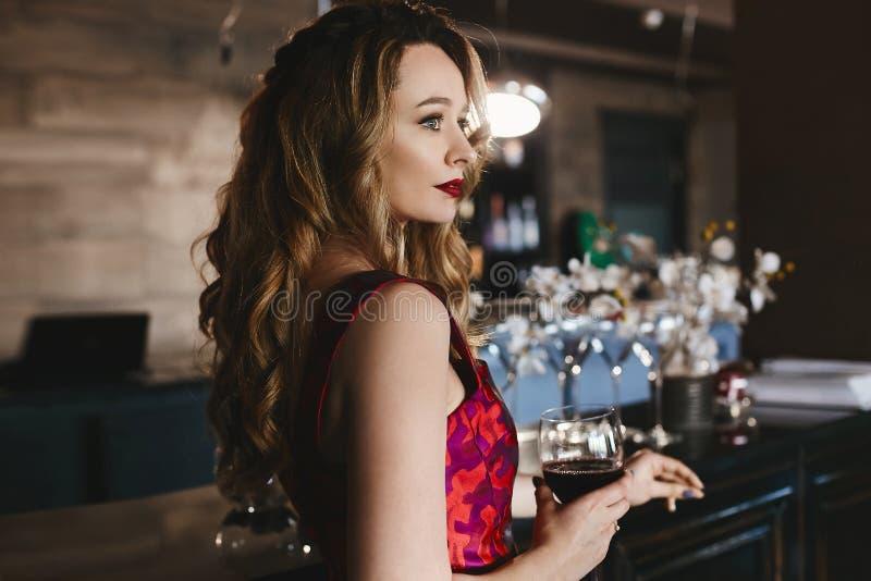 Modna blondynka modela dziewczyna z seksownymi czerwonymi wargami z kędzierzawą fryzurą w menchii sukni stojakach przy barem z i, zdjęcie royalty free