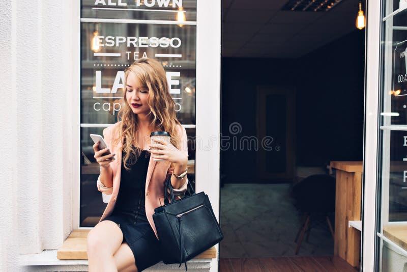 Modna blondynki dziewczyna w czerni sukni siedzieć plenerowy w kawiarni Trzyma filiżankę, używać telefon, patrzeje cieszącą się obrazy royalty free