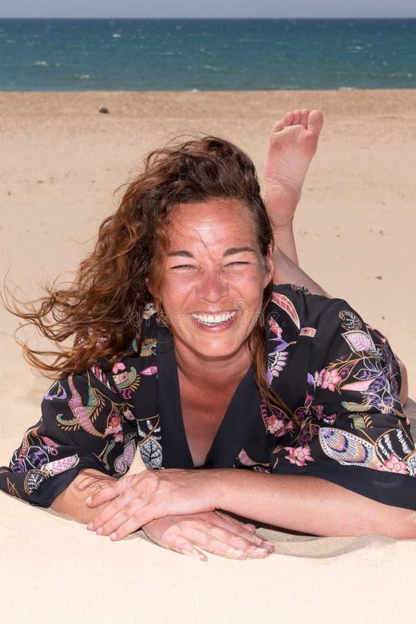 Modna brunetki kobieta na piaskowatej plaży ono uśmiecha się szczęśliwy obrazy royalty free