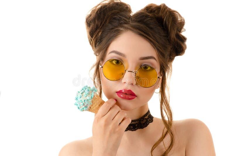 Modna brunetki kobieta w round szkłach z lody w ręce fotografia royalty free