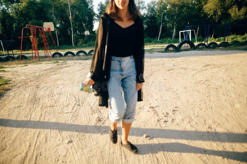 Modna chłodno kobieta relaksuje z czarnymi okularami przeciwsłonecznymi i drelichowymi cajgami, ostrość przy boiskiem Elegancki m obrazy royalty free