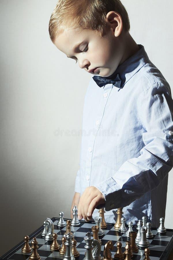Modna chłopiec bawić się szachy dzieciak mądrze Mały genialny dziecko Inteligentna gra czarny deskowego czeka koniec gry biznesow zdjęcia stock