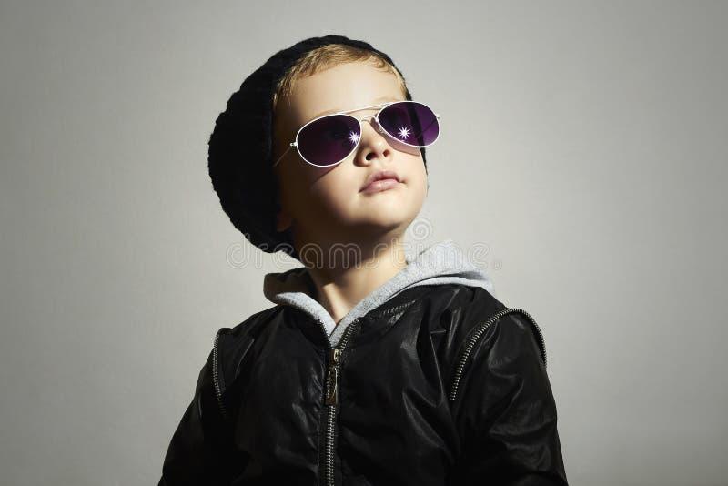 Modna chłopiec w okularach przeciwsłonecznych kochanie Pozować małego modela w czarnej nakrętce fotografia stock