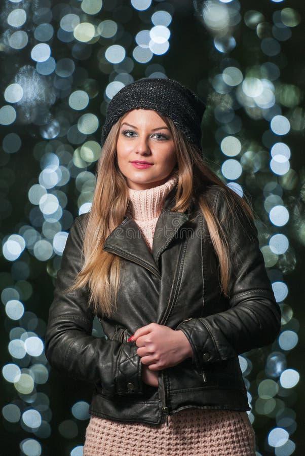 Modna dama jest ubranym nakrętkę i czarną kurtkę z błękitem plenerowych w xmas scenerii zaświeca w tle. Portret młoda dziewczyna obrazy stock