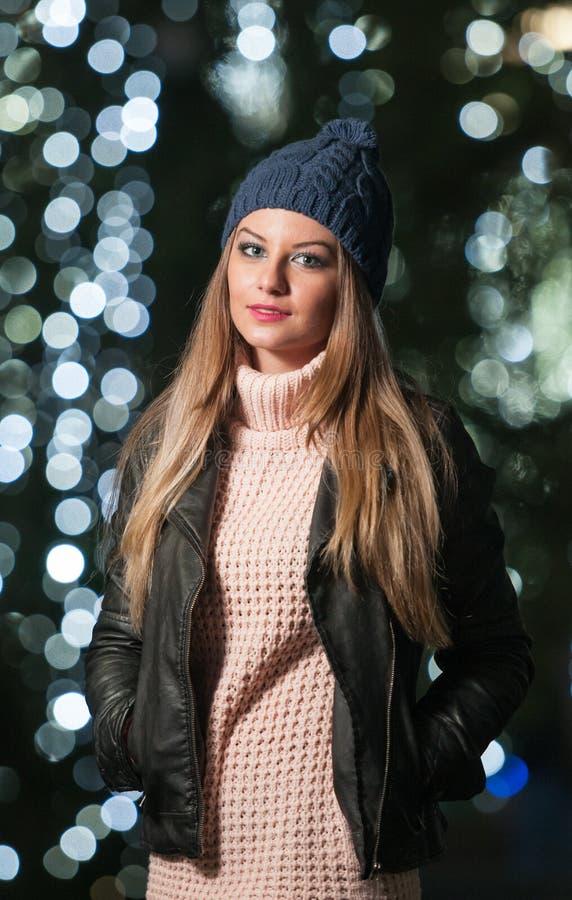Modna dama jest ubranym nakrętkę i czarną kurtkę z błękitem plenerowych w xmas scenerii zaświeca w tle. Portret młoda kobieta fotografia stock