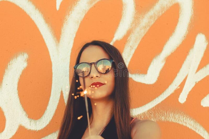 Modna dziewczyna jest ubranym okulary przeciwsłonecznych z sparkler w ręce obraz stock