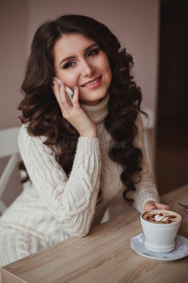 Modna dziewczyna opowiada na telefonie, cieszący się życie, odpoczywa Kobieta z filiżanką kawy i telefonem w ręce zdjęcia stock