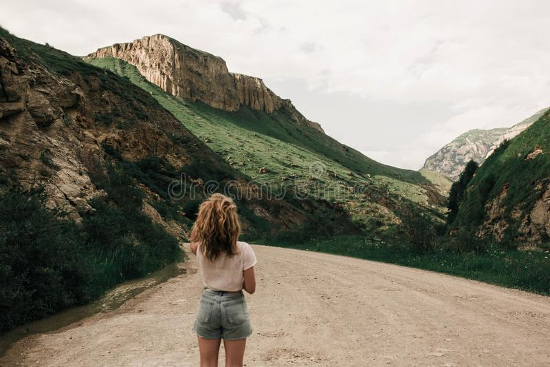 Modna dziewczyna stoi na drodze w średniogórzach w biel ubraniach Zielona trawa i góry zdjęcia royalty free