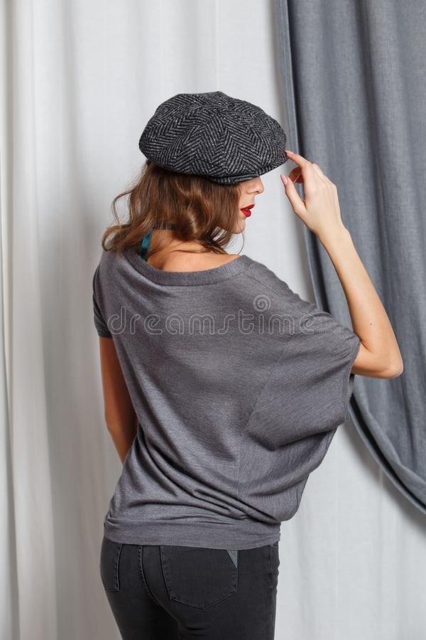 Modna dziewczyna ubiera? w eleganckiej szarej bluzce z zielonymi koralikami, szarymi cajgami i nakr?tki eleganckimi pozami w stud fotografia stock