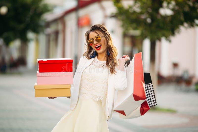 Modna dziewczyna w okularach przeciwsłonecznych z obuwianymi pudełkami i torba na zakupy w t fotografia royalty free