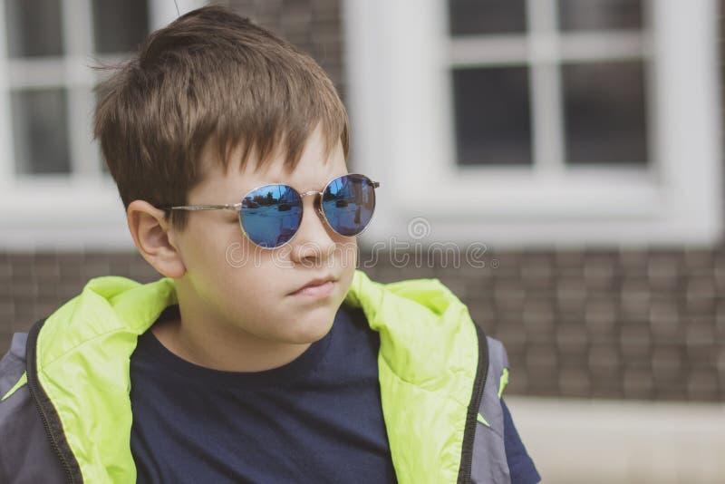 Modna elegancka duża chłopiec w okularach przeciwsłonecznych outdoors w lecie fotografia royalty free