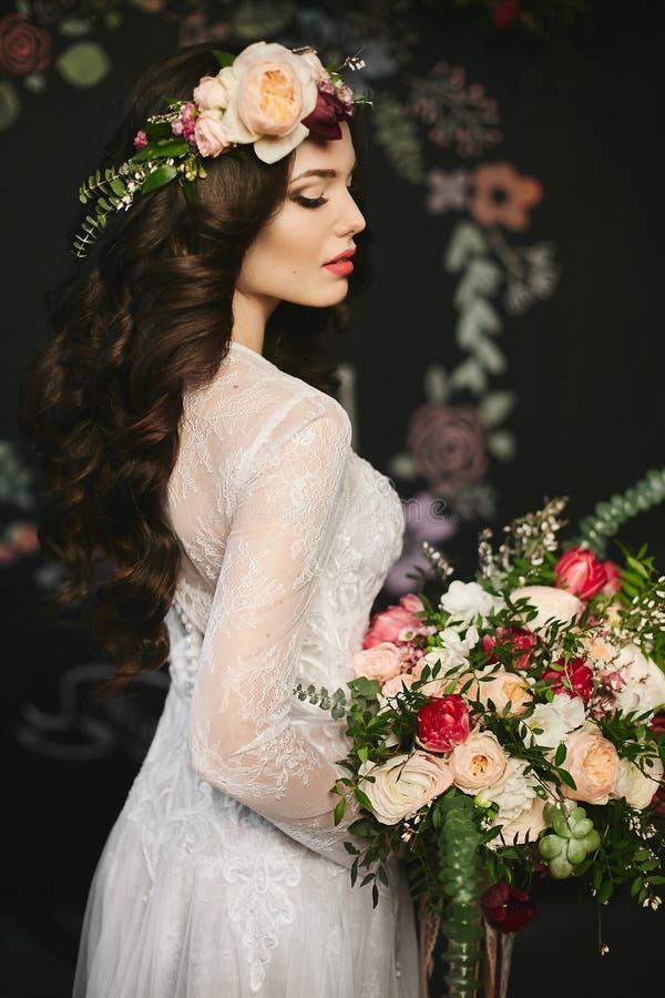 Modna i piękna brunetka modela dziewczyna z jaskrawym makeup z kwiecistym wiankiem na jej głowie w eleganckiej koronce i fotografia stock