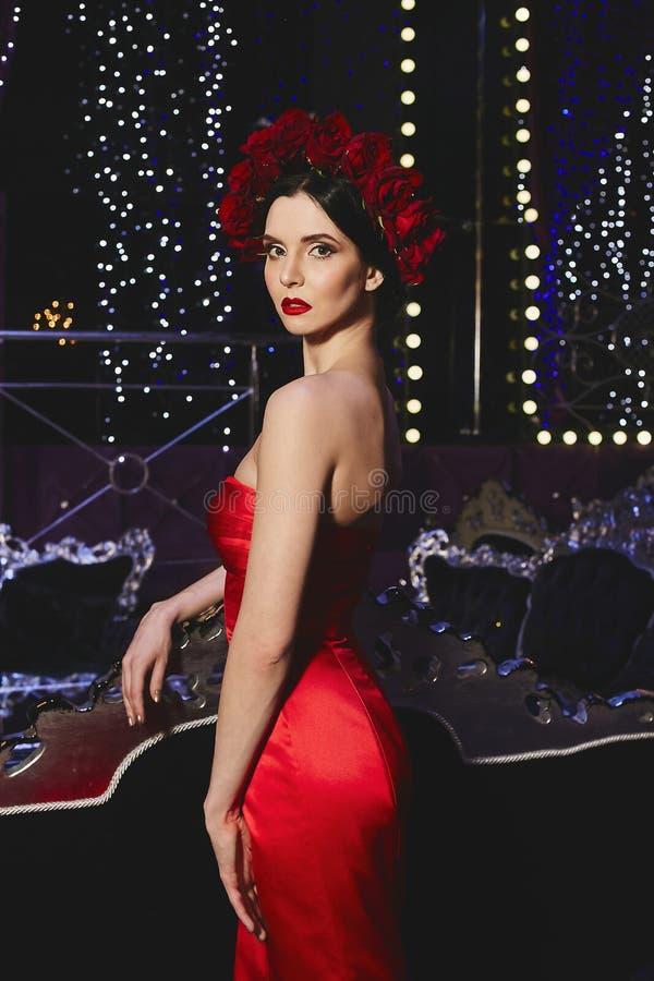 Modna i seksowna brunetki schudnięcia modela dziewczyna z jaskrawym makeup z wiankiem czerwoni kwiaty na jej głowie w czerwieni i zdjęcie royalty free