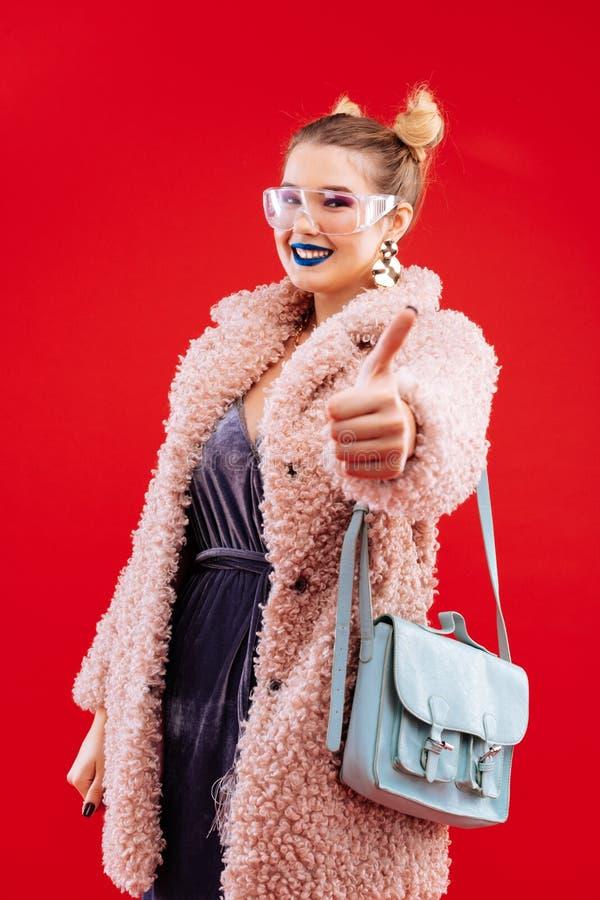Modna kobieta jest ubranym różowego puszystego żakiet i błękitną torbę zdjęcia royalty free